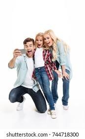 Full length portrait of a cheerful young family with a child standing together and taking a selfie isolated over white background