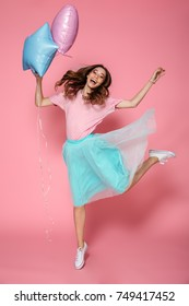 Full length portrait of a cheerful young girl in bright colorful clothes holding air balloons while jumping and looking at camera isolated over pink background