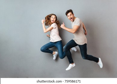 Full length portrait of a cheerful young couple jumping and running over gray wall
