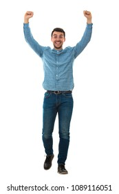 Full length portrait of a cheerfull young man raising his hands up like a winner isolated on white background.