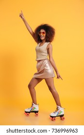 Full length portrait of a cheery afro american woman dressed in retro clothes and wearing skates while standing and dancing isolated over yellow background