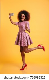 Full length portrait of a cheery afro american woman in retro style clothes showing victory gesture and posing while standing and taking a selfie isolated over yellow background