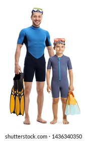 Full length portrait of a child and man in wetsuits standing and holding diving flippers isolated on white background