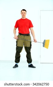 Full length portrait of a cleaner in a uniform with a broom isolated white background