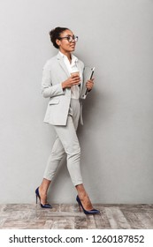 Full length portrait of a confident african business woman wearing suit standing over gray background, holding takeaway coffee, carrying laptop