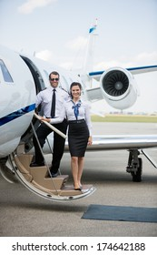 Full length portrait of confident airhostess and pilot standing on private jet's ladder at airport terminal