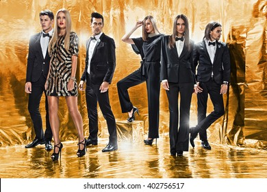 Full length portrait of a confident business team standing on a gold background