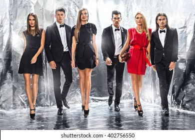 Full length portrait of a confident business team standing on a silver background