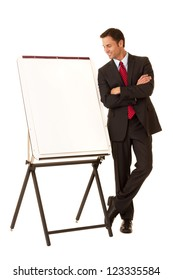 Full length portrait of a confident businessman on a white backdrop standing next to a presentation easel looking at the page on the easel
