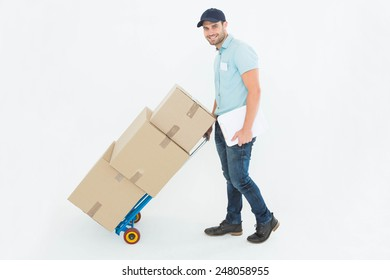 Full length portrait of confident delivery man pushing trolley of boxes on white background