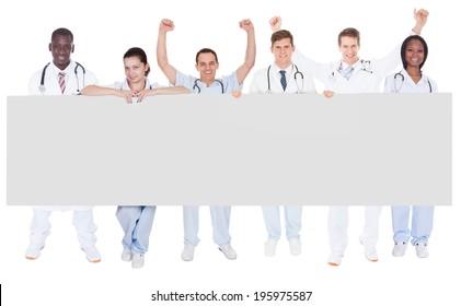 Full length portrait of confident doctors holding blank billboard over white background