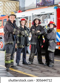 Full length portrait of confident firefighters standing arms crossed at fire station