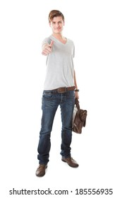 Full length portrait of confident male student gesturing thumbs up against white background