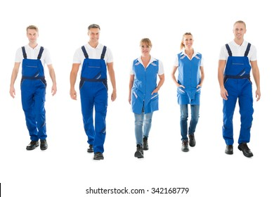 Full length portrait of confident male and female janitors walking in row against white background