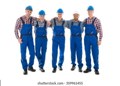 Full length portrait of confident male carpenters standing with arms around against white background