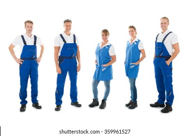 Full length portrait of confident male and female janitors standing in row against white background