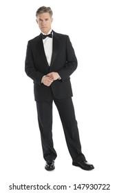 Full length portrait of confident mature man wearing tuxedo isolated over white background