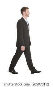 Full length portrait of confident mid adult businessman walking over white background