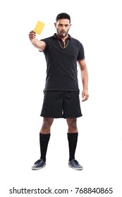 Full length portrait of confident mixed race soccer referee showing yellow card and blowing whistle while standing against white background