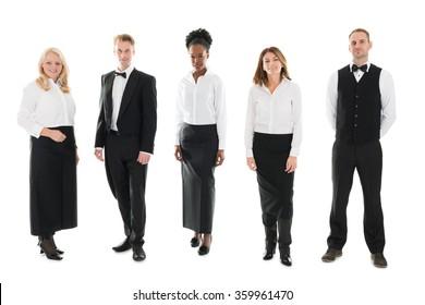 Full length portrait of confident multi ethnic restaurant staff standing against white background