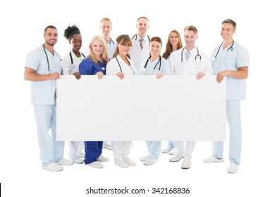 Full length portrait of confident multiethnic medical team holding blank billboard against white background