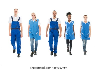 Full length portrait of confident multiethnic janitors walking in row against white background