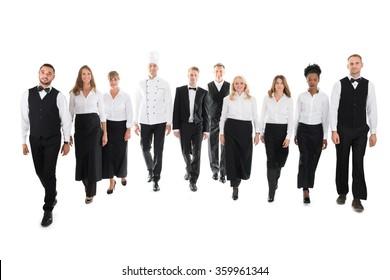 Full length portrait of confident restaurant staff walking in row against white background