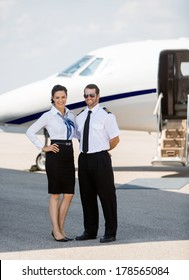 Full length portrait of confident stewardess and pilot standing against private jet at terminal