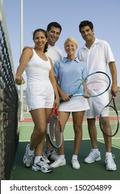 Full length portrait of confident tennis players with rackets and ball on court