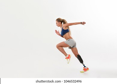 Full length portrait of a confident young disabled sportswoman running fast isolated over white background