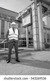 Full length portrait of confident young male engineer standing outside industry