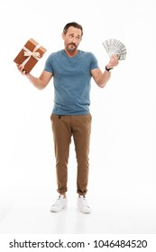 Full length portrait of a confused mature man dressed in t-shirt holding present box and bunch of money banknotes isolated over white background