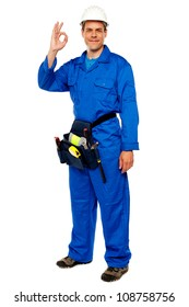 Full length portrait of construction worker gesturing okay sign, carrying tools bag