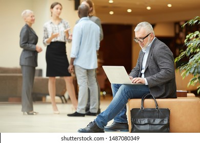 Full length portrait of contemporary senior businessman using laptop while working in lobby or office hall, copy space