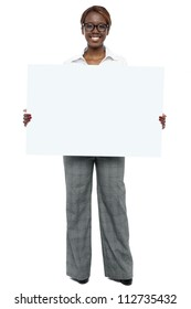 Full length portrait of corporate woman holding blank white billboard
