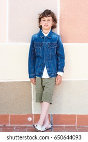Full length portrait of curly-haired boy in denim jacket and Bermuda shorts standing over modern painted wall in the street.