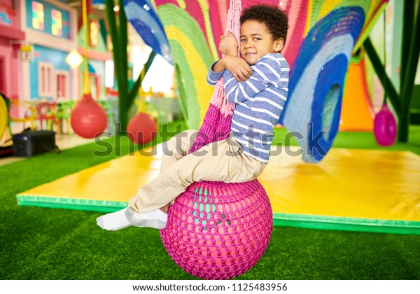 Full length portrait of cute African-American boy enjoying funny swings while having fun in indoor play area, copy space