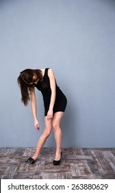 Full length portrait of a cute drunk woman in fashion black dress. Over gray wall. Sleeping while standing