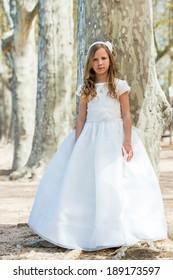 Full length portrait of cute girl in white dress in forest.