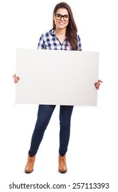 Full length portrait of a cute hipster brunette wearing glasses and holding a white sign