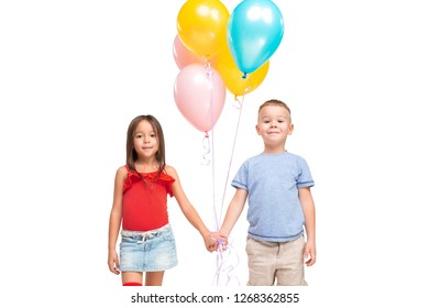 Full length portrait of cute little kids girl and boy in stylish clothes looking at camera and smiling, standing against white studio wall with Balloons. Kids fashion concept