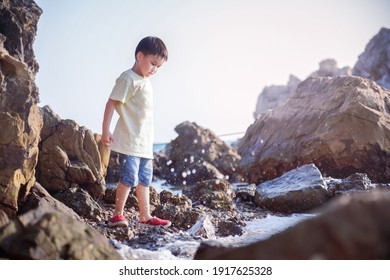 Full length portrait of cute little active asian boy standing on the rocks at the beach looking at sea water crashing to the shore during beautiful sunny day in summer time