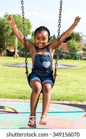Full length portrait of cute Little african child swinging in park.