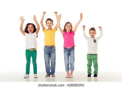 Full length portrait of cute little kids in casual clothes keeping hands up, looking at camera and smiling, isolated on a white background