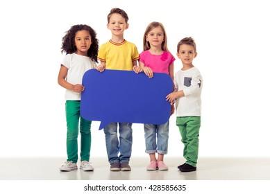 Full length portrait of cute little kids in casual clothes holding blue speech bubble, looking at camera and smiling, isolated on a white background