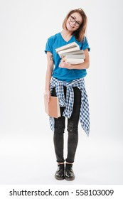 Full length portrait of a cute smiling girl holding stack of books isolated on the white background