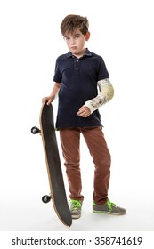 Full length portrait of a cute young boy holding a skateboard with a broken arm  isolated on white background
