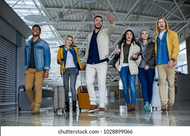 Full length portrait of delighted males and females looking for exit in the airport. They are walking in the hall with luggage, one man is pointing out