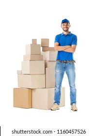 Full length portrait of delivery man standing near stack of boxes isolated on white background