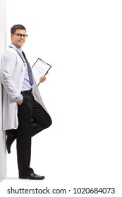 Full length portrait of a doctor leaning against a wall isolated on white background